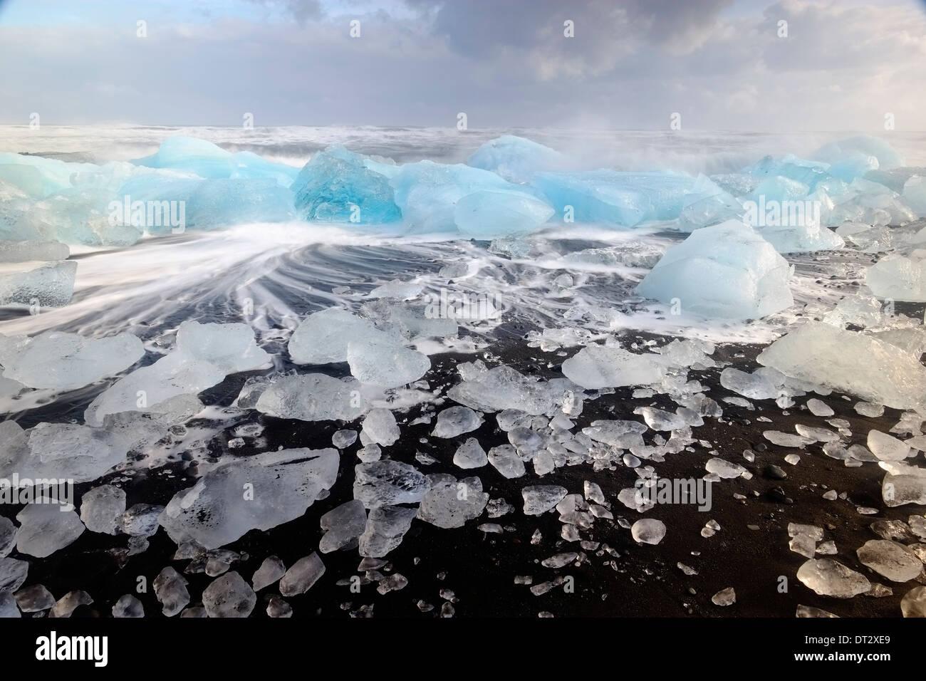 Iceberg e onde sulla spiaggia di Jokulsarlon, regione polare, Sud Islanda Immagini Stock
