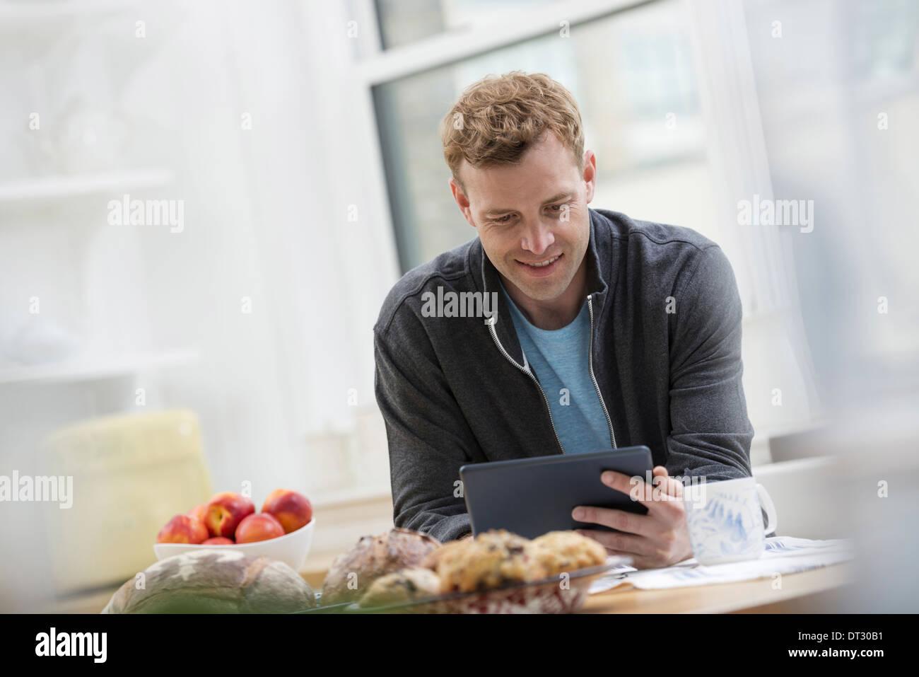 In un ufficio o un interno dell appartamento a New York City un uomo in una felpa alto utilizzando un tampone digitale appoggiato su di un bar per la prima colazione Immagini Stock
