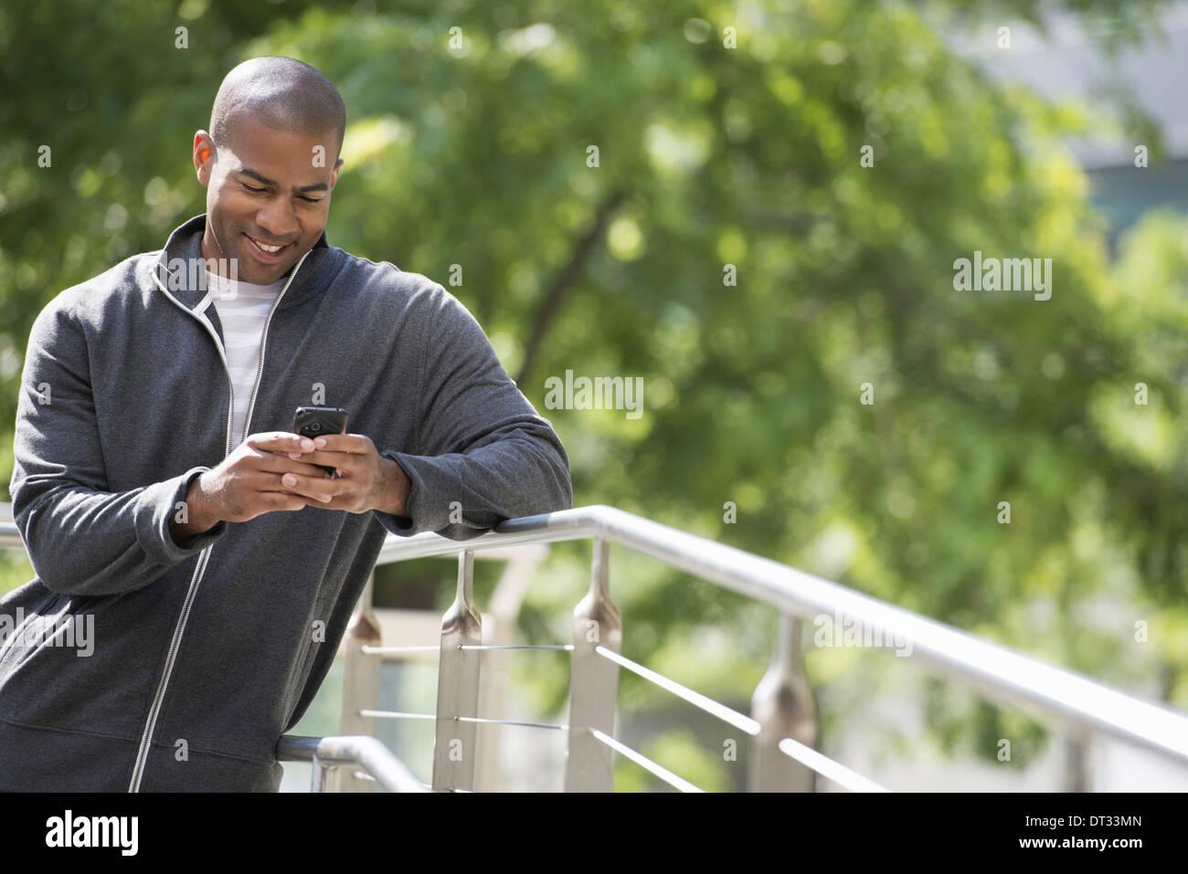 Un uomo in una felpa guardando al suo smart phone Immagini Stock