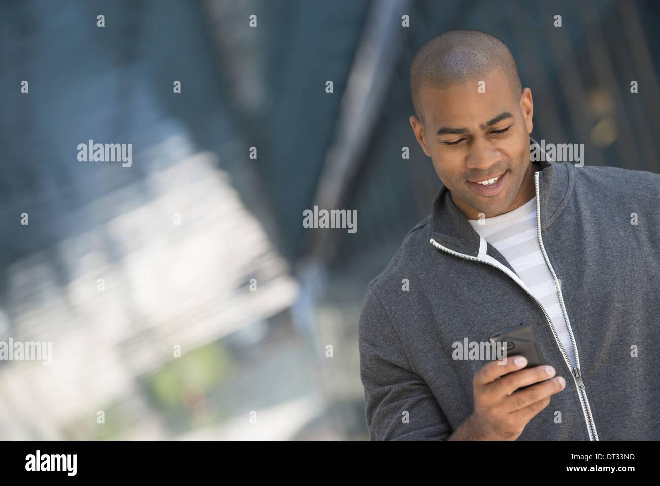 Un uomo in grigio Felpa con zip utilizzando il suo smart phone Immagini Stock