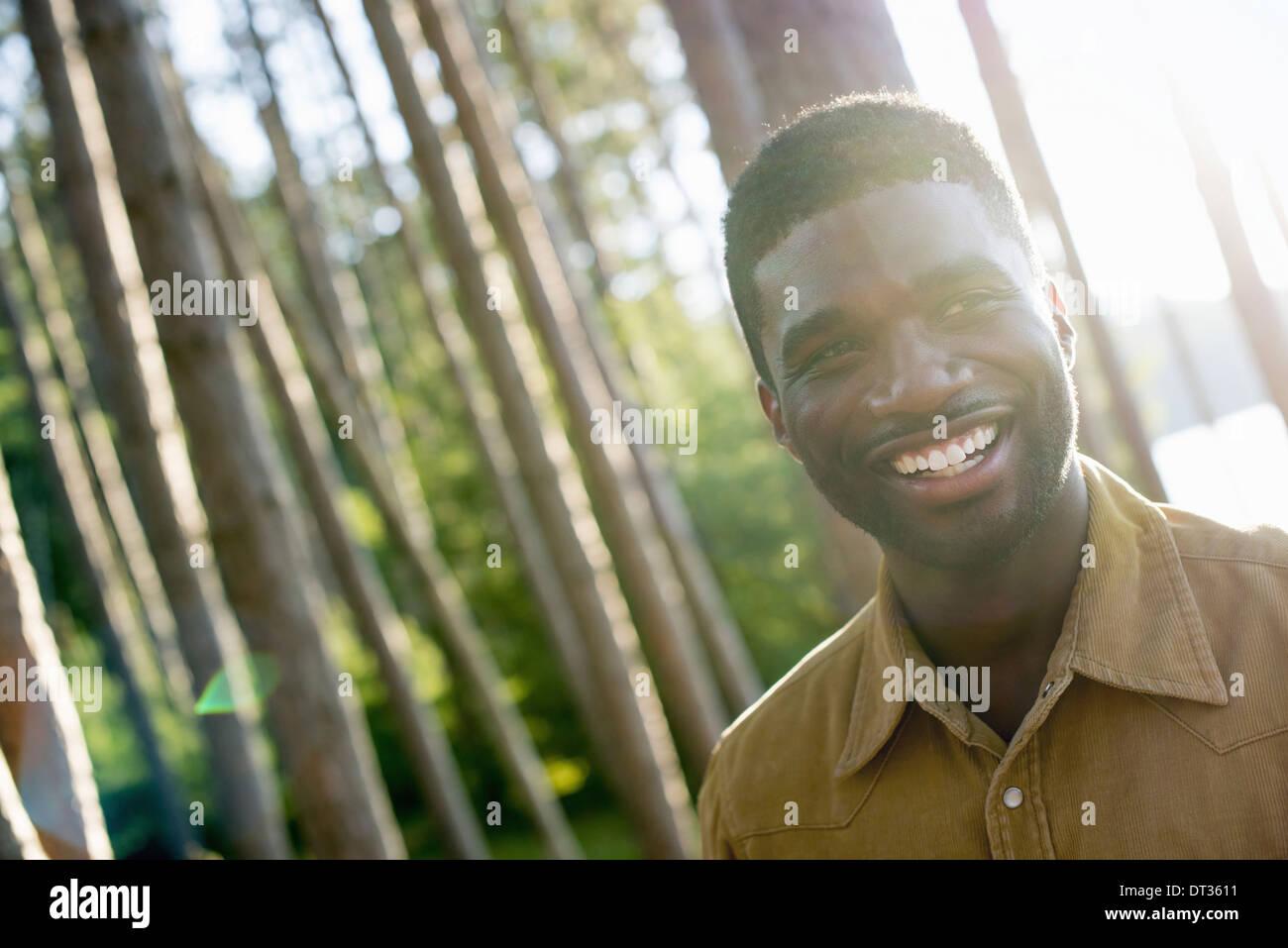 Un uomo sorridente con la videocamera sotto l'ombra degli alberi in estate Immagini Stock