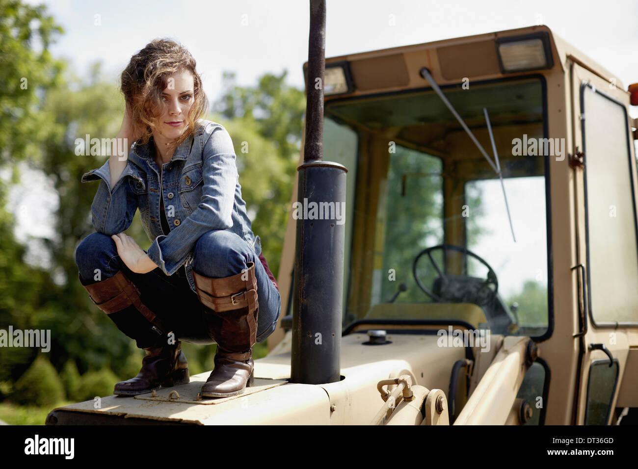 Una giovane donna in denim camicia e stivali su il cofano di un trattore Immagini Stock