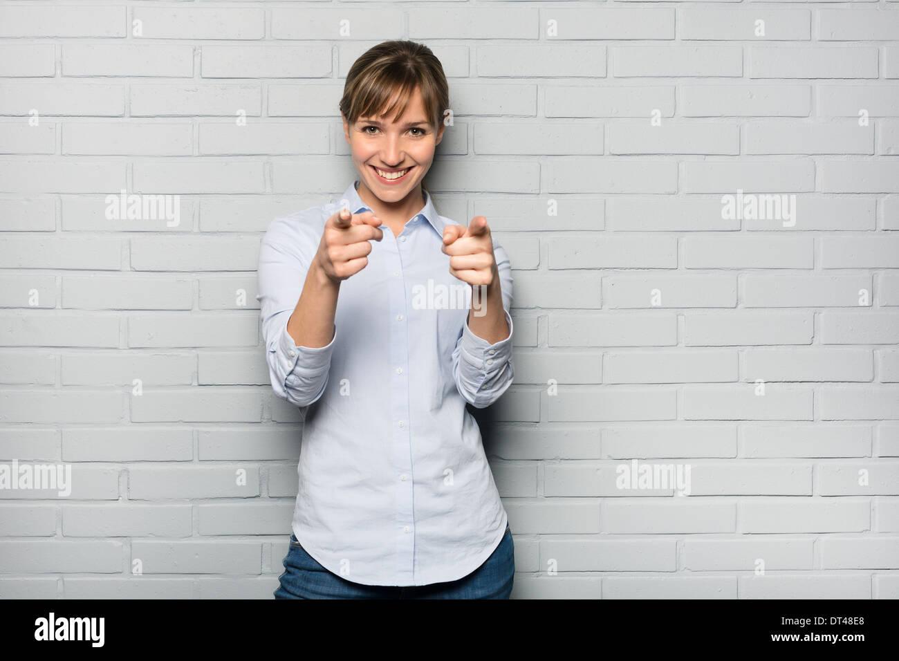 Donna informale studio felici puntare il dito lo sfondo grigio Immagini Stock