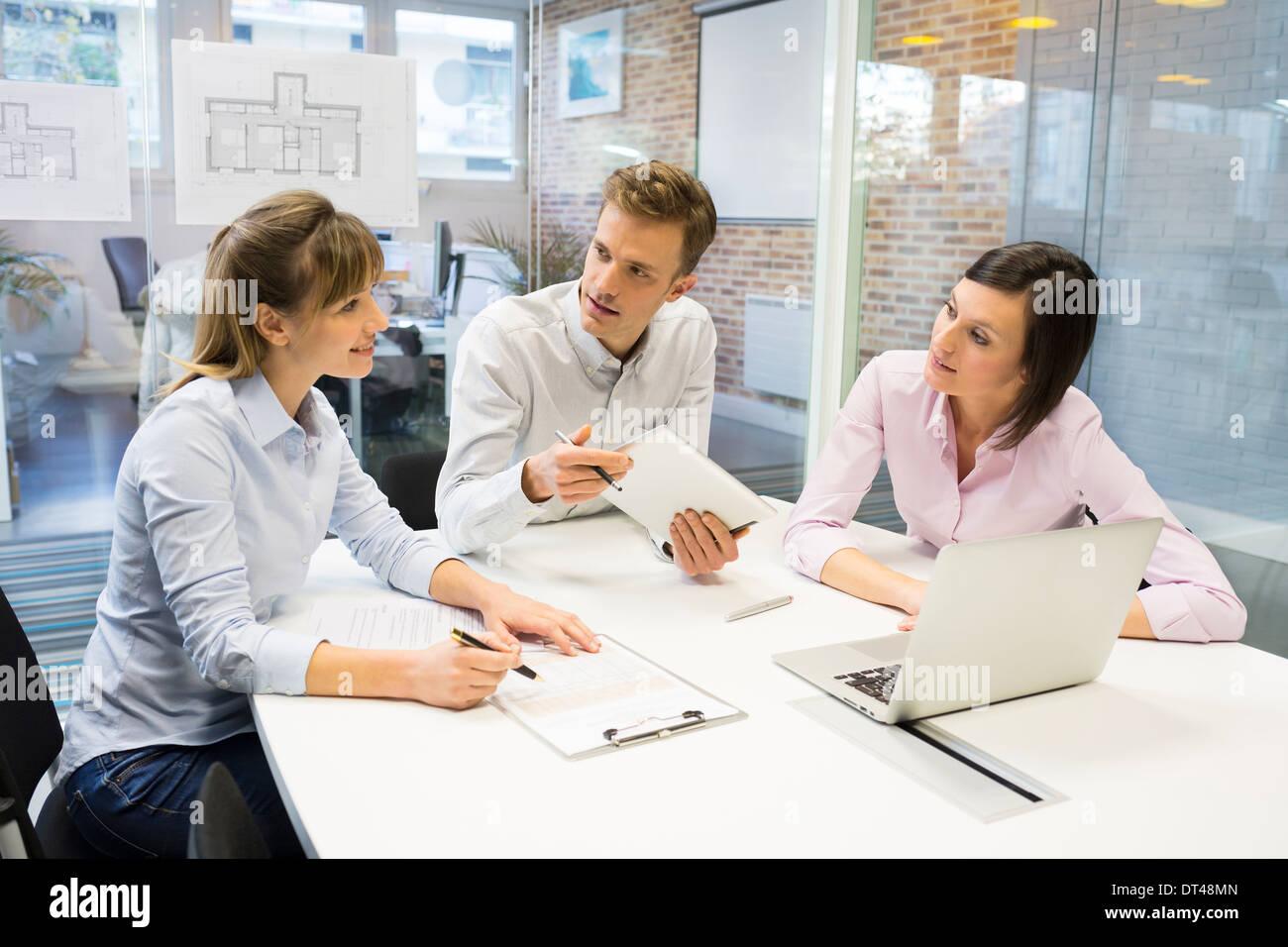Imprenditrice imprenditore reunion scrivania portatile ai colleghi Immagini Stock