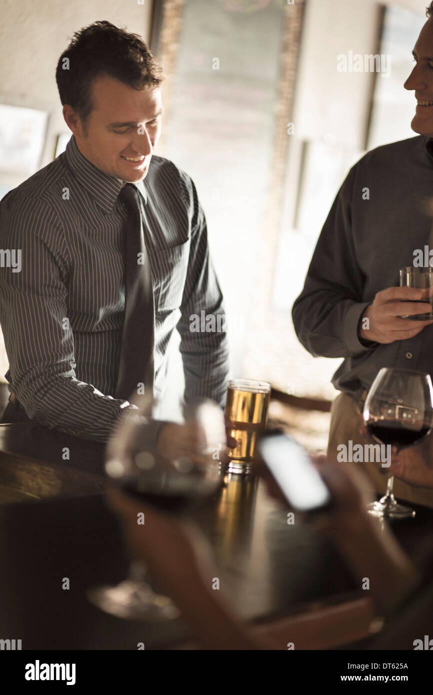 Business gli amici sorseggiando un drink in un bar di vino Immagini Stock