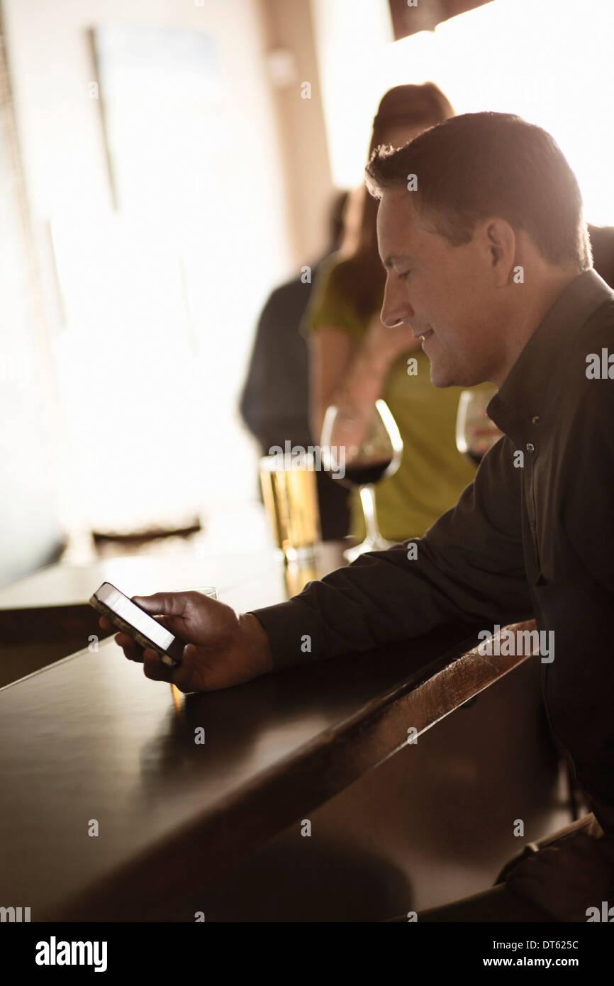 Imprenditore guardando il cellulare in un wine bar Immagini Stock