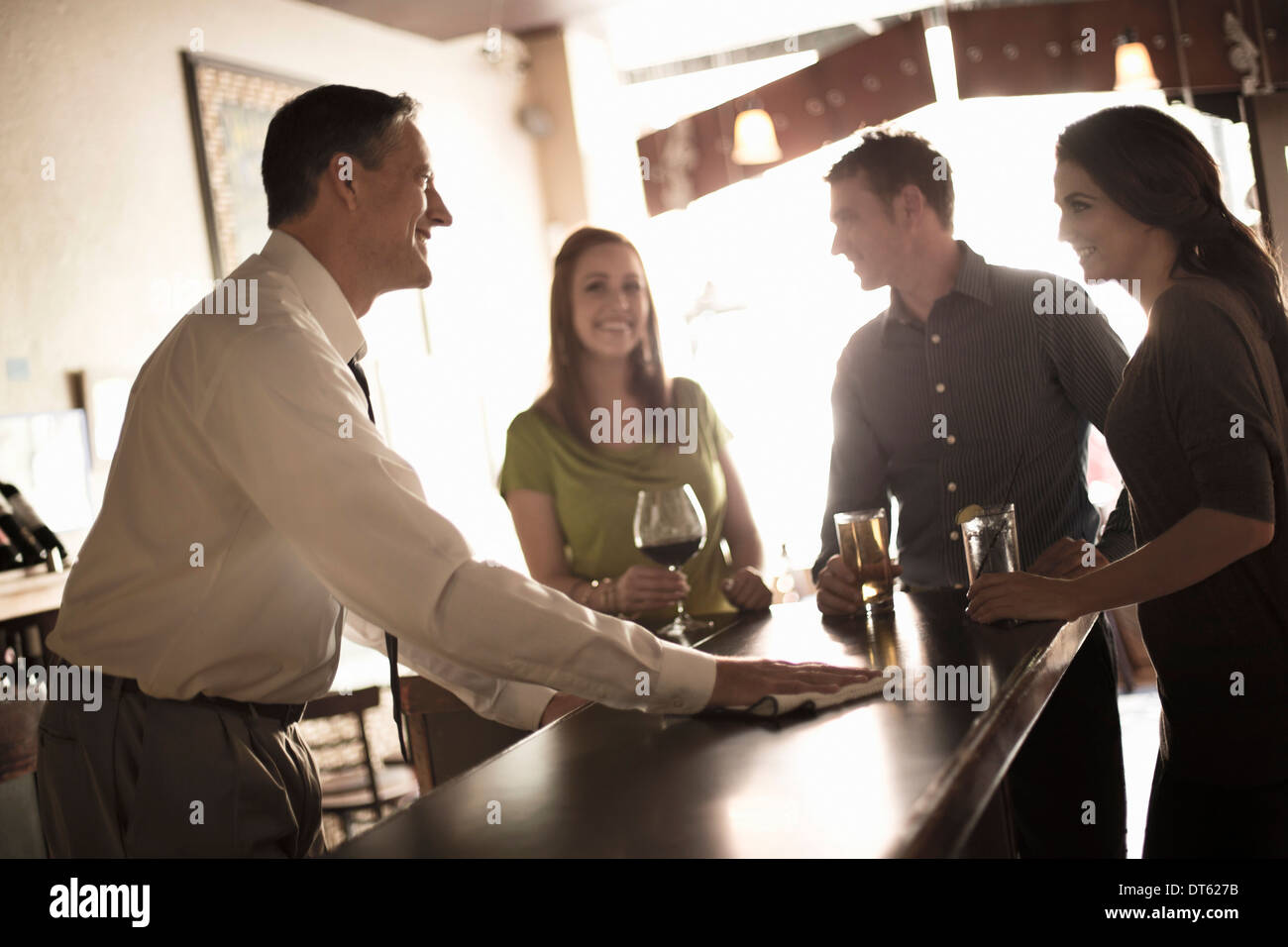 Gli amici sorseggiando un drink nel bar del vino Immagini Stock