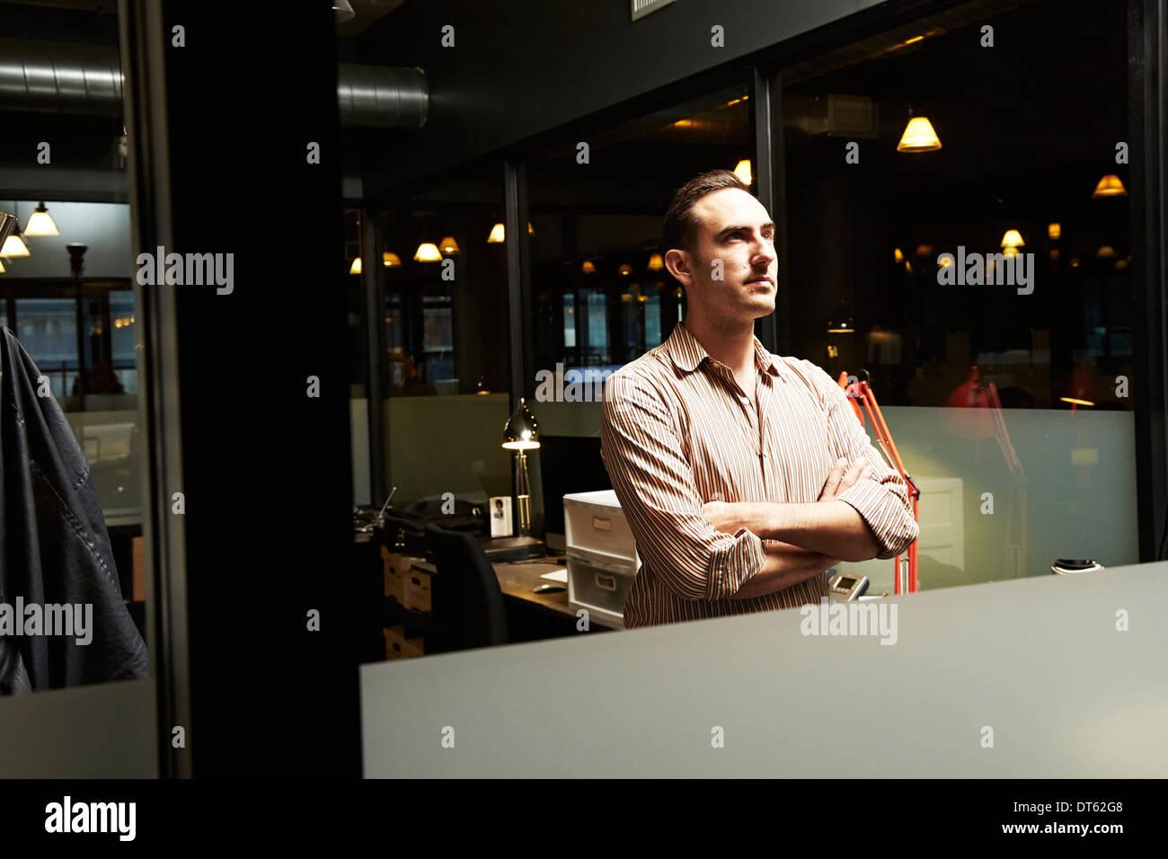 Ritratto di imprenditore con le braccia incrociate che guarda lontano Immagini Stock