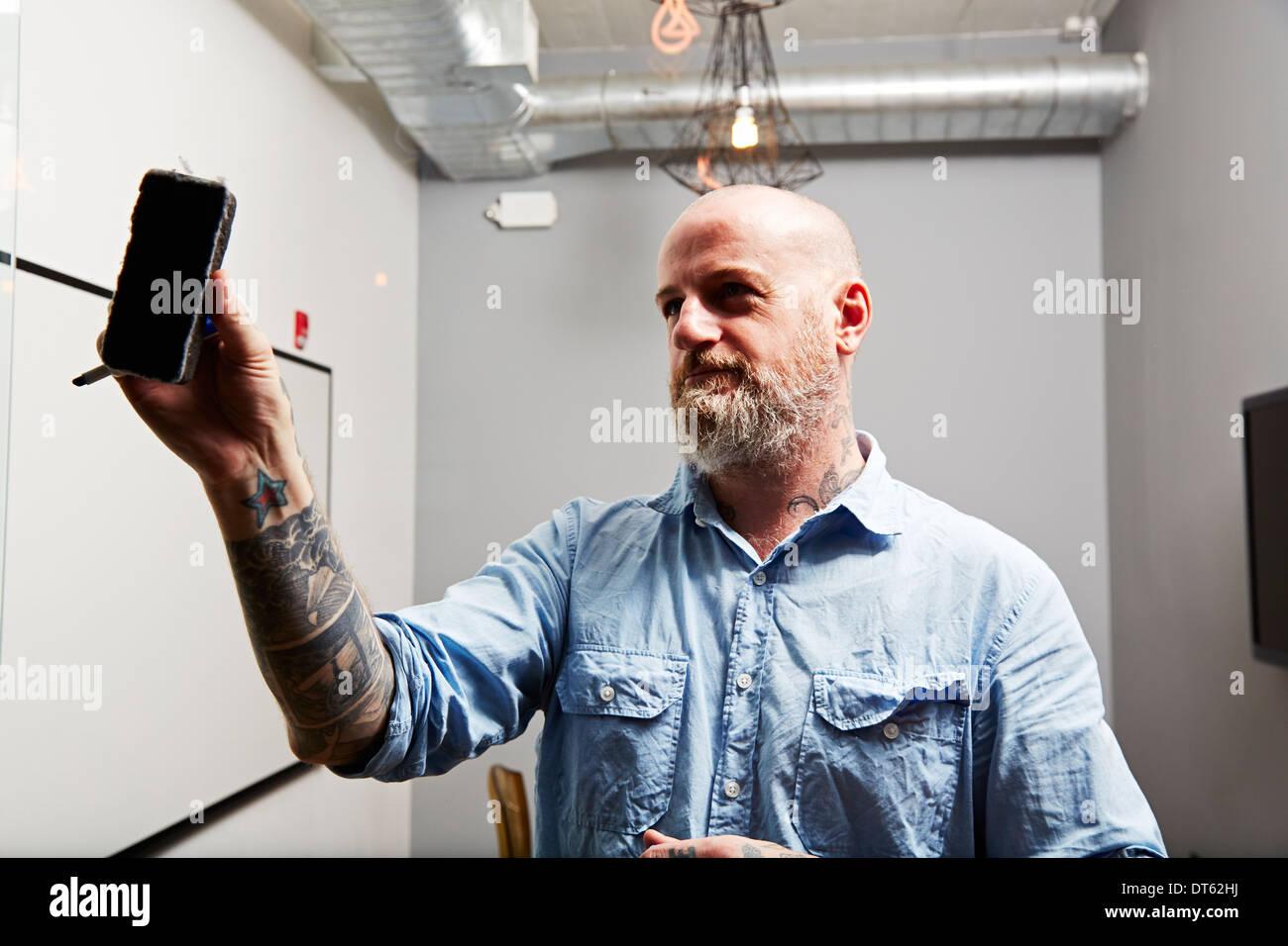 Uomo maturo mediante whiteboard eraser Foto Stock
