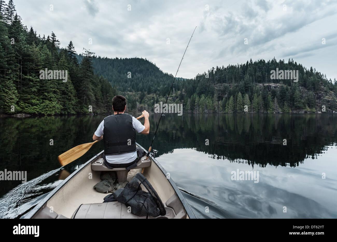 Giovane uomo pesca Lago Buntzen, British Columbia, Canada Immagini Stock
