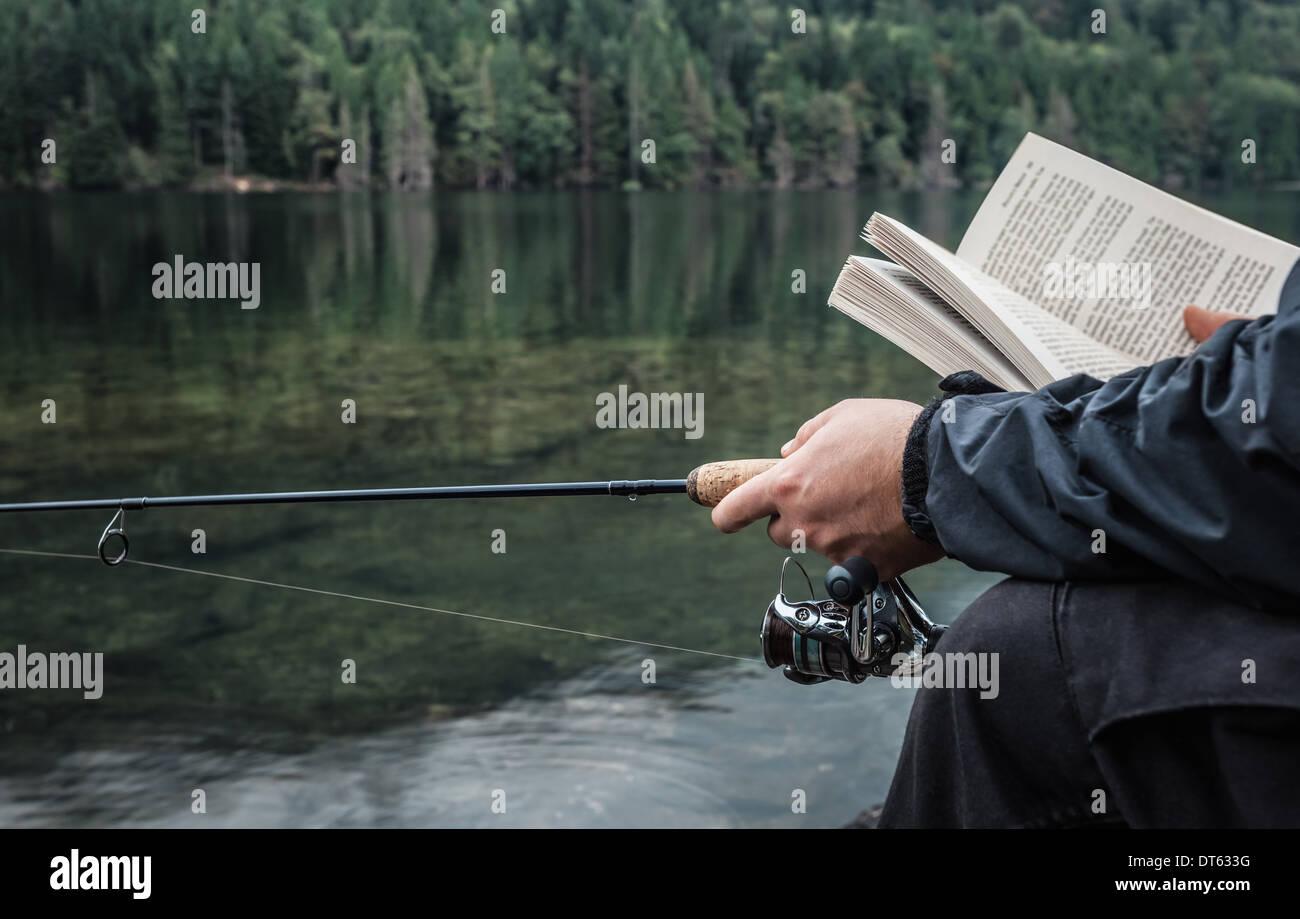 L'uomo la pesca con Libro, Lago Buntzen, British Columbia, Canada Immagini Stock