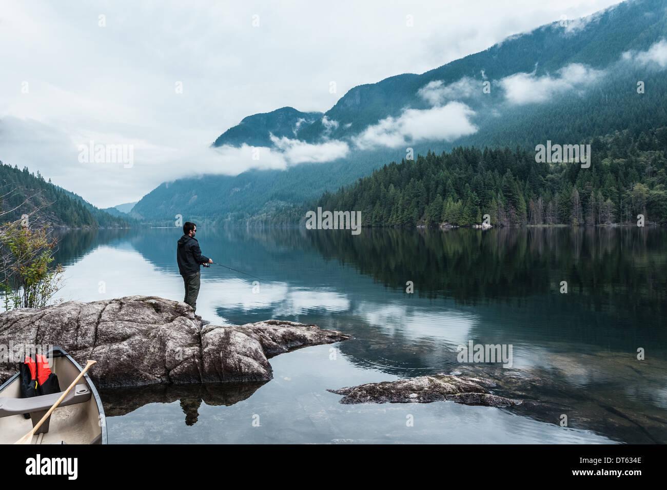 L'uomo pesca dalle rocce, Lago Buntzen, British Columbia, Canada Immagini Stock