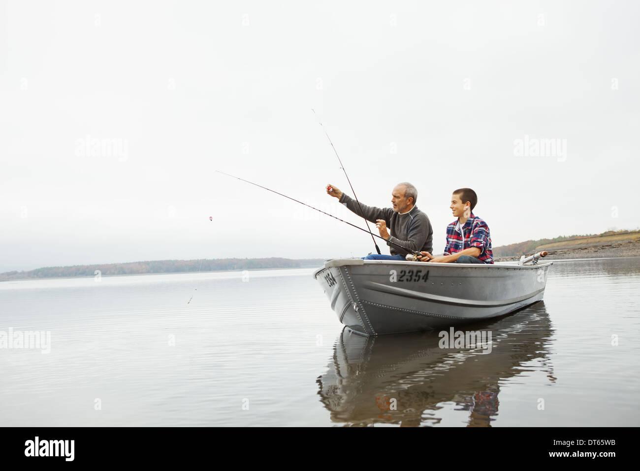 Una giornata al lago Ashokan. Un uomo e un ragazzo adolescente pesca dalla barca. Immagini Stock