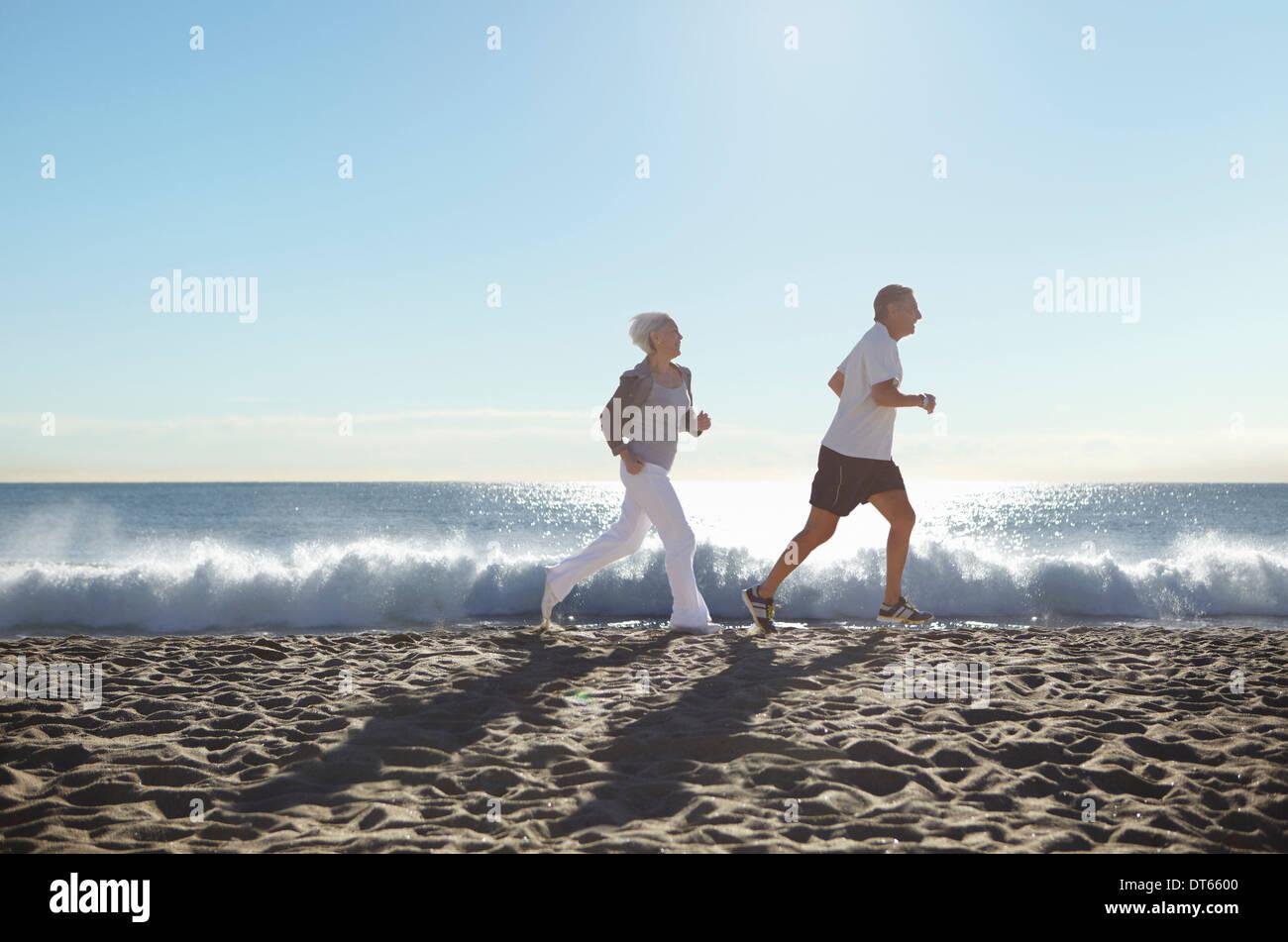 Giovane jogging sulla spiaggia Immagini Stock