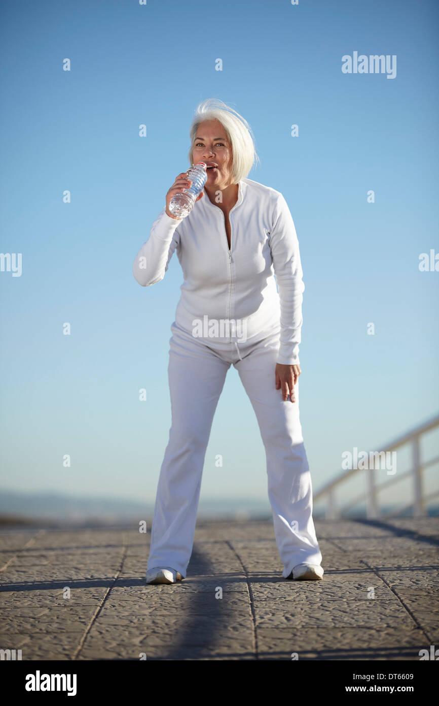 Donna matura acqua potabile a piedi Immagini Stock