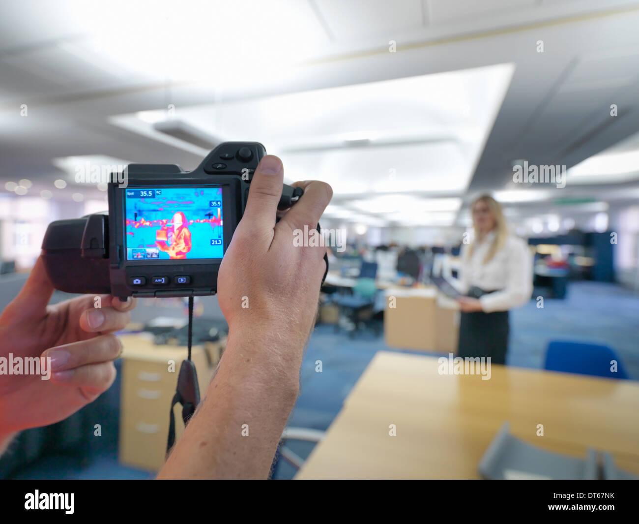 Ufficio lavoratori tenendo termica immagini a infrarossi in ufficio per controllare il rendimento termico Immagini Stock