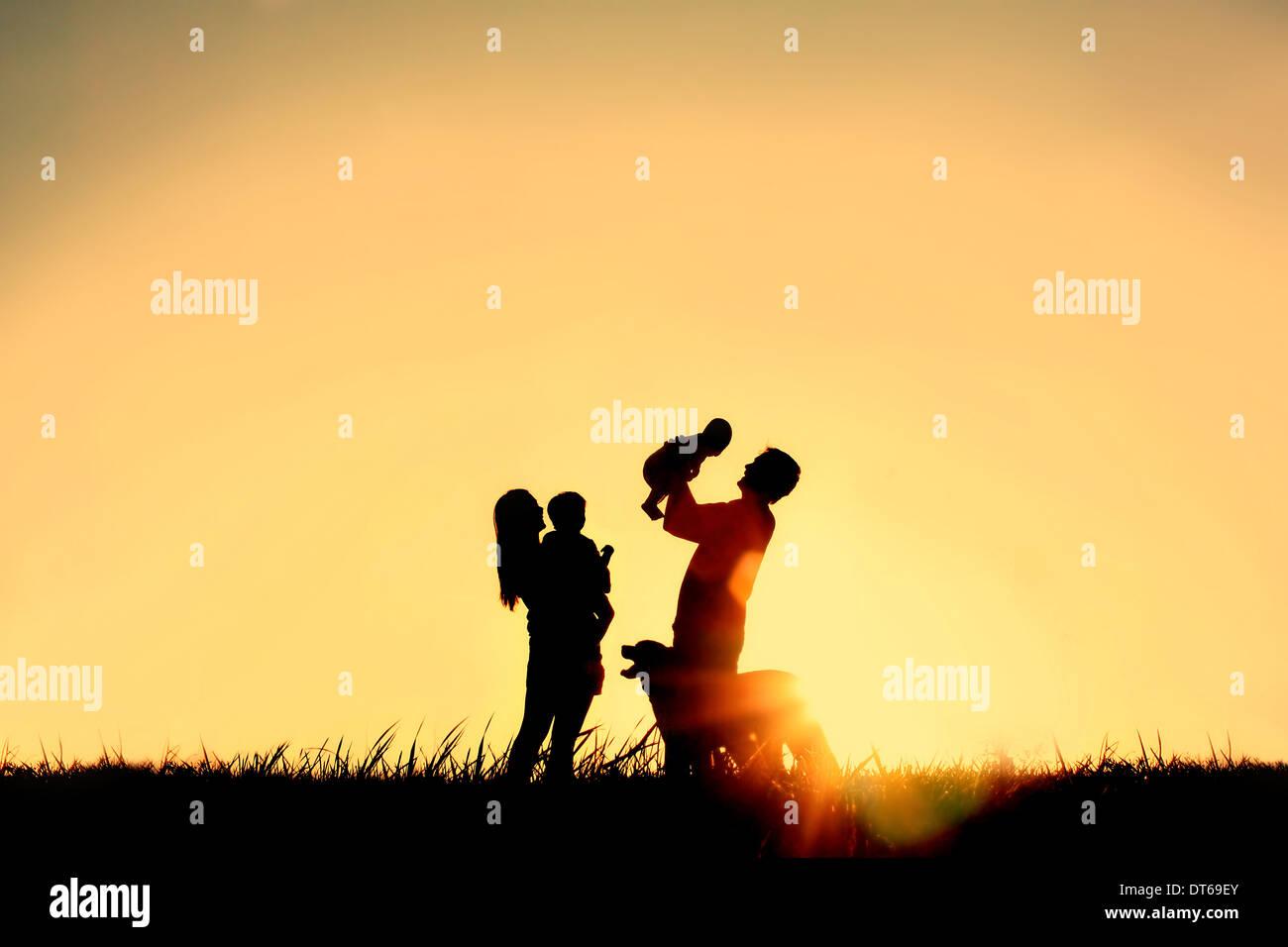 La silhouette di una felice famiglia di quattro persone, madre, padre, baby, e il bambino ed il loro cane davanti a un cielo sunsetting, Immagini Stock