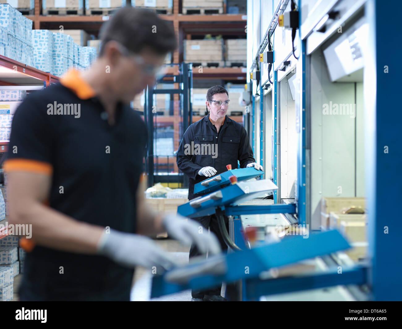 Ingegneri scegliere i pezzi dal magazzino automatizzato in fabbrica Immagini Stock