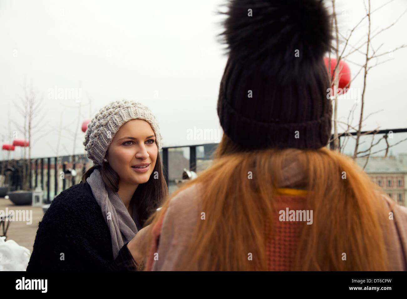 Due giovani donne adulte in chat sulla terrazza sul tetto Immagini Stock
