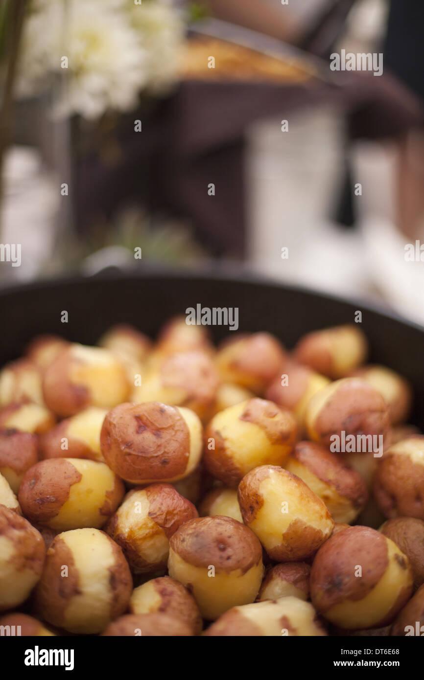Un matrimonio un pranzo a buffet. Un piatto di parzialmente Pelate le patate di primizia. Immagini Stock