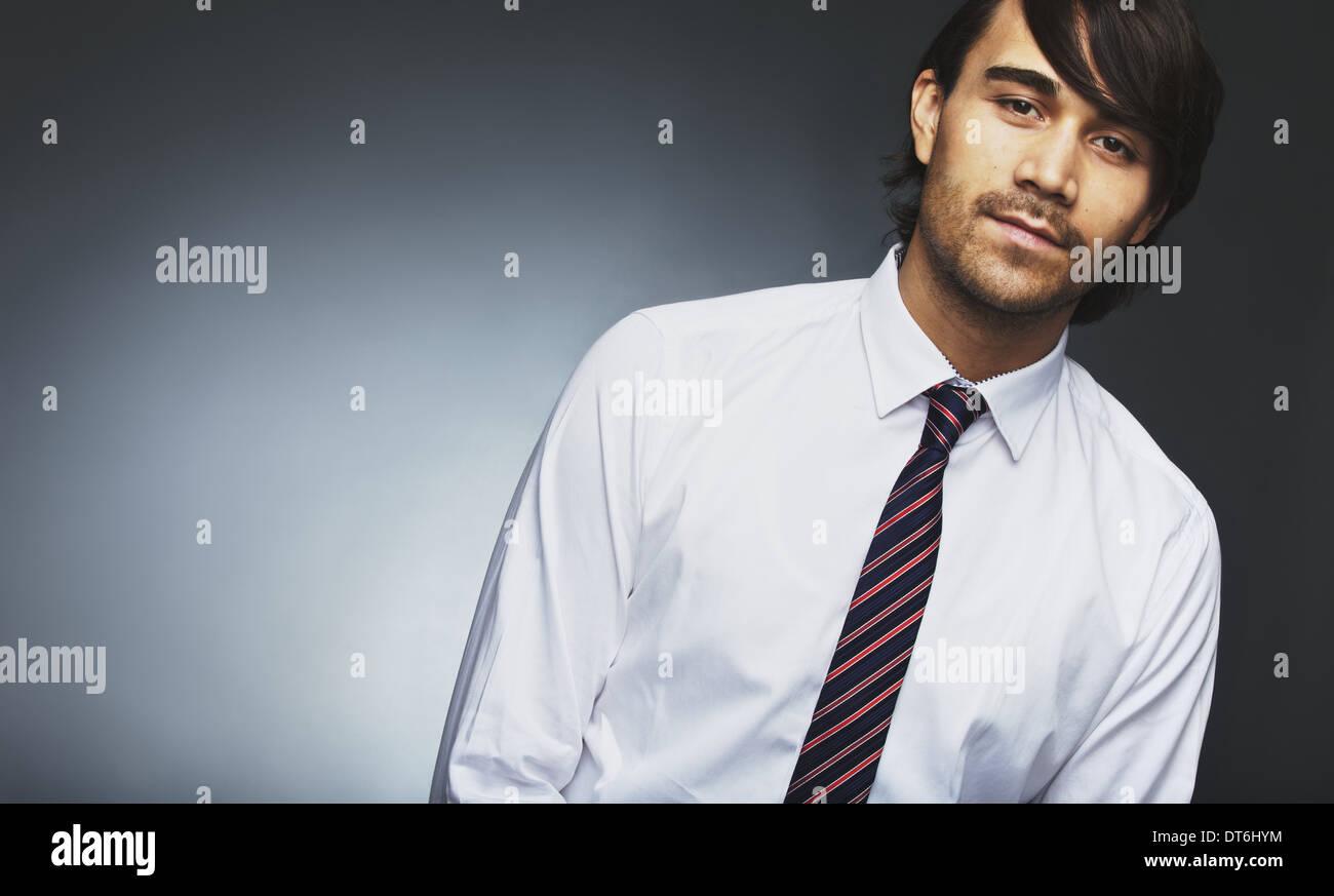 Immagine del giovane maschio modello di usura formale guardando la fotocamera. Razza mista imprenditore in posa contro uno sfondo grigio. Immagini Stock