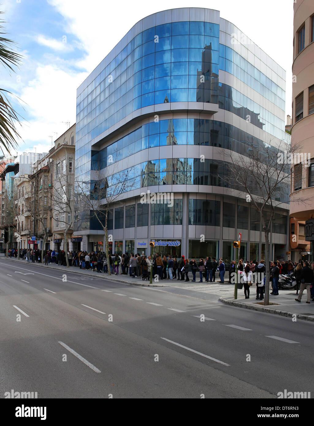 Le persone attendono in coda il loro turno di applicare per un'offerta di lavoro nell'isola di Mallorca, Spagna Immagini Stock