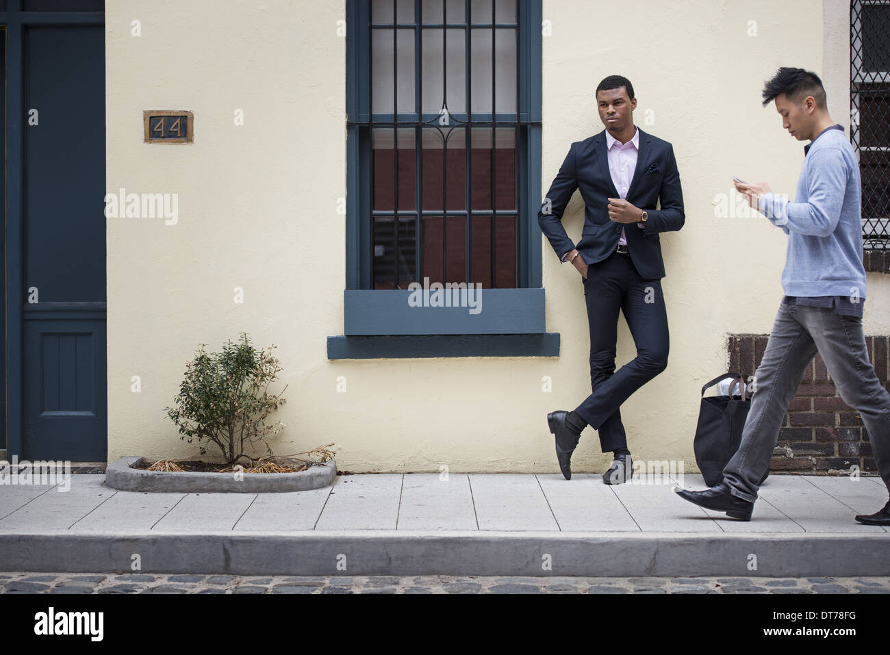 I giovani all'aperto lungo le strade della città in primavera. Uomo appoggiato a un muro e un passato a piedi controllando il suo telefono. Immagini Stock