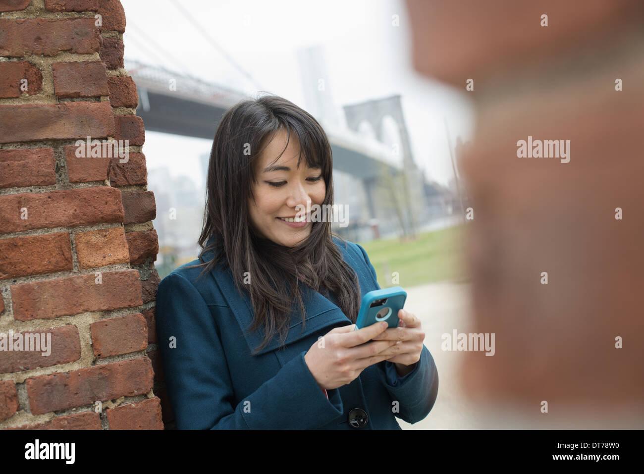 La città di New York. Il Ponte di Brooklyn attraversando la East River. Una donna appoggiata contro un muro di mattoni, controllando il suo telefono. Immagini Stock