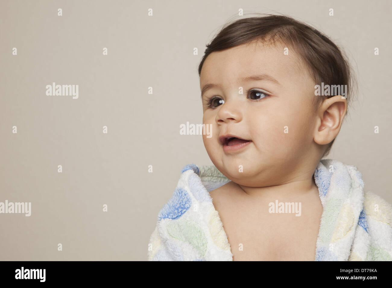 Un 8 mese vecchio baby boy con un asciugamano da bagno avvolto intorno a lui. Immagini Stock
