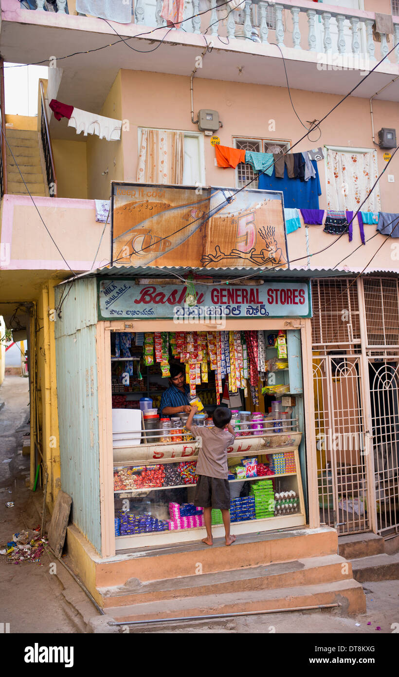 Ragazzo indiano dolci di acquisto da un negozio. Puttaparthi, Andhra Pradesh, India Immagini Stock