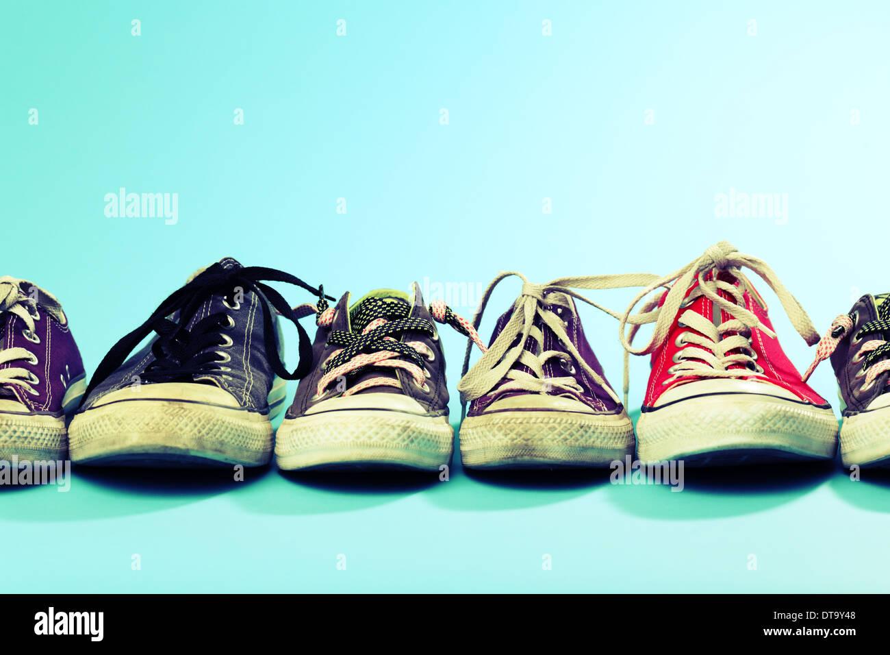 Una linea di Converse scarpe di diverse dimensioni e colori sparato contro  uno sfondo blu. f62afaf7ec1