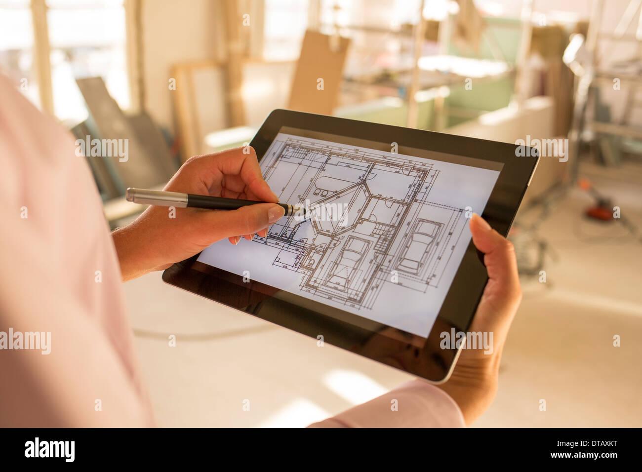 Architetto donna disegno con lo stilo sulla tavoletta elettronica nel sito in costruzione Immagini Stock