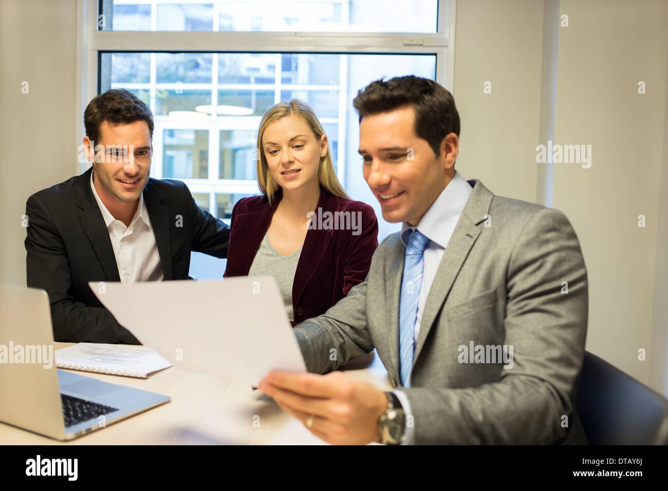 Immobili che mostra il contratto alla coppia giovane, nuovi proprietari Immagini Stock