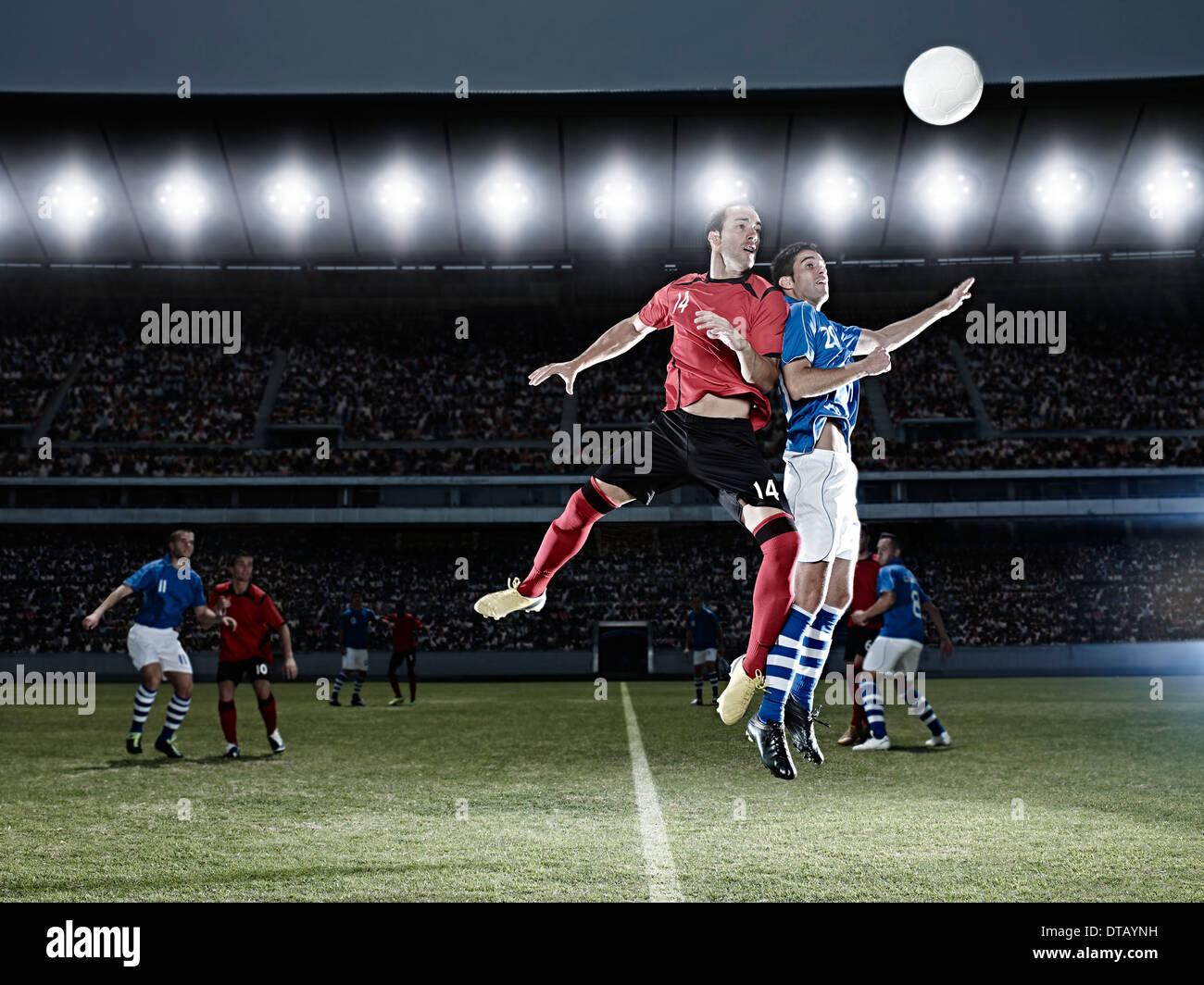 I giocatori di calcio saltando per la palla sul campo Immagini Stock