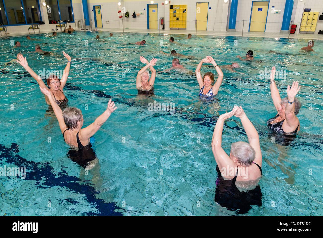 Un gruppo di donne pratiche di ginnastica in acqua in una piscina. Immagini Stock