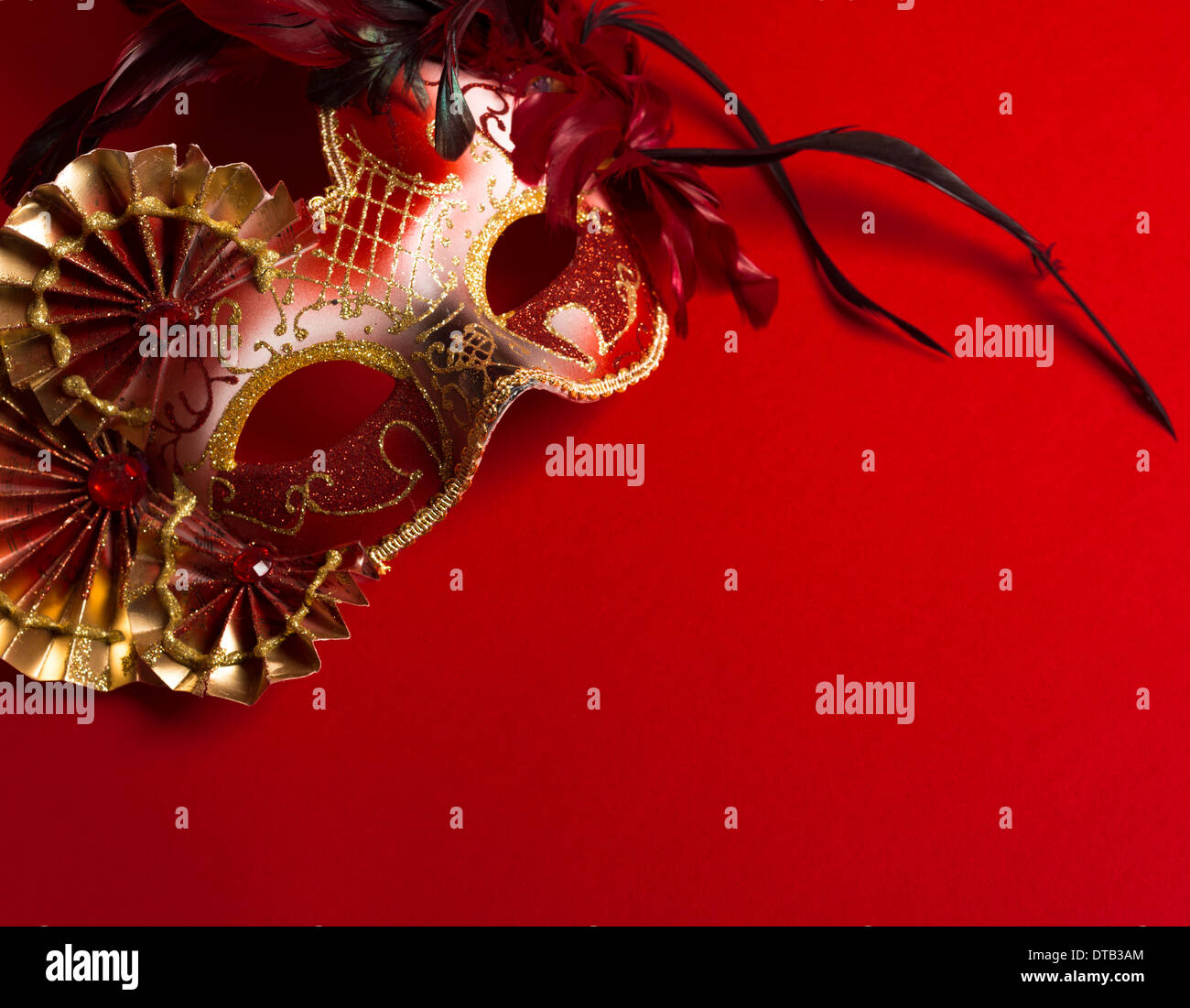 Un rosso e oro veneziano, Mardi Gras maschera su uno sfondo rosso Immagini Stock