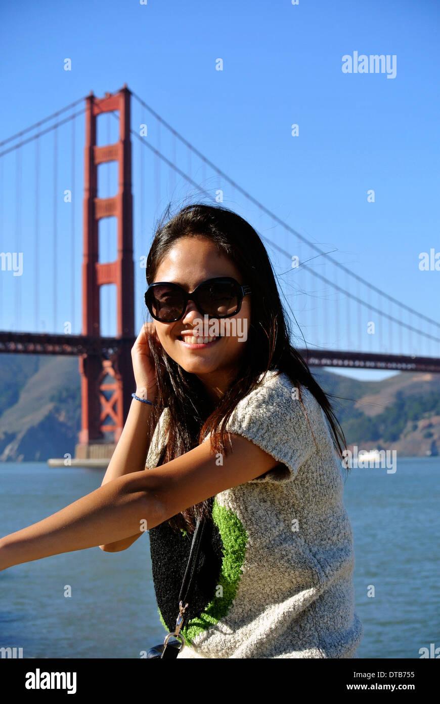 Bella ragazza cinese pone per il fotografo con un telefono cellulare nella parte anteriore del Golden Gate Bridge Immagini Stock