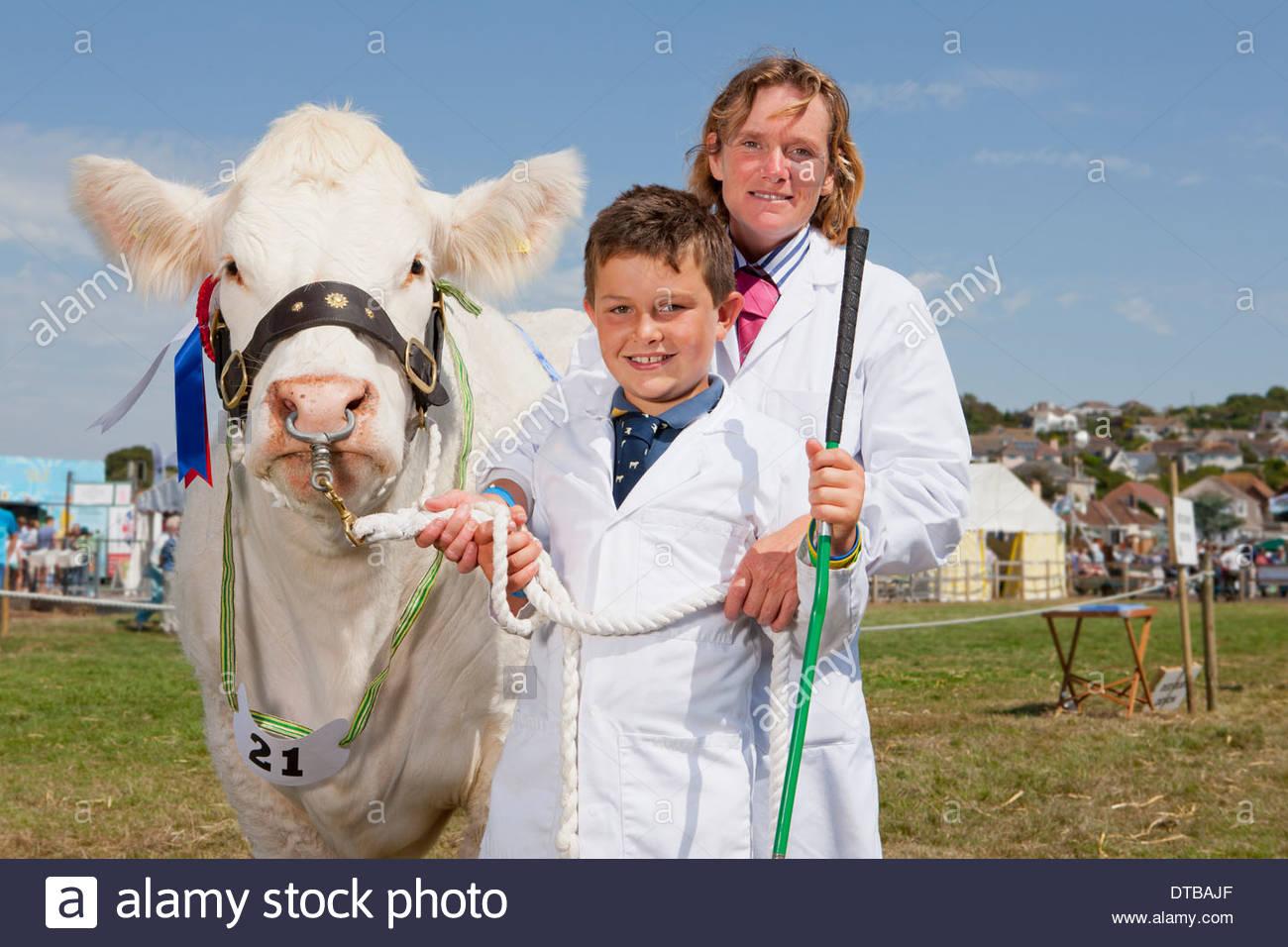 La madre e il figlio con il vincitore del premio vacca a spettacolo agricolo Immagini Stock