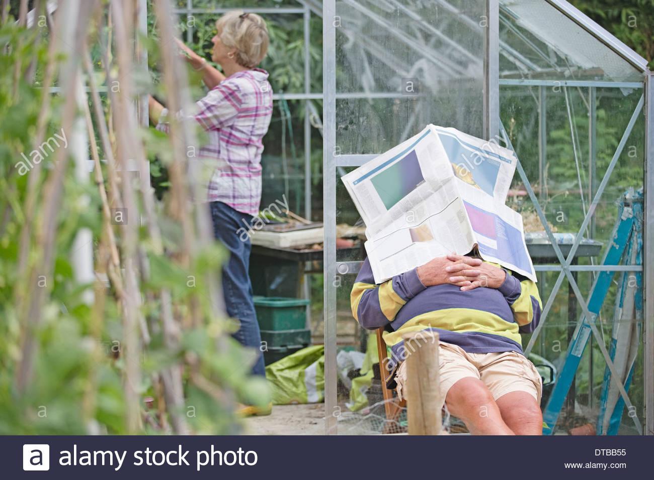 Senior uomo addormentato in un Orto mentre la moglie lavora Foto Stock