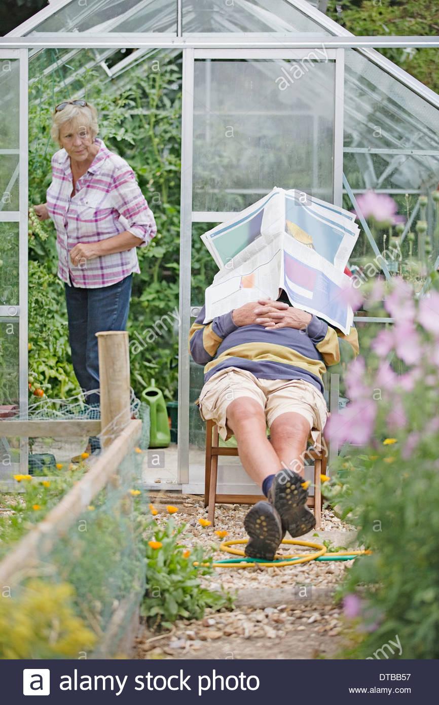 Senior uomo addormentato in un Orto mentre la moglie lavora Immagini Stock