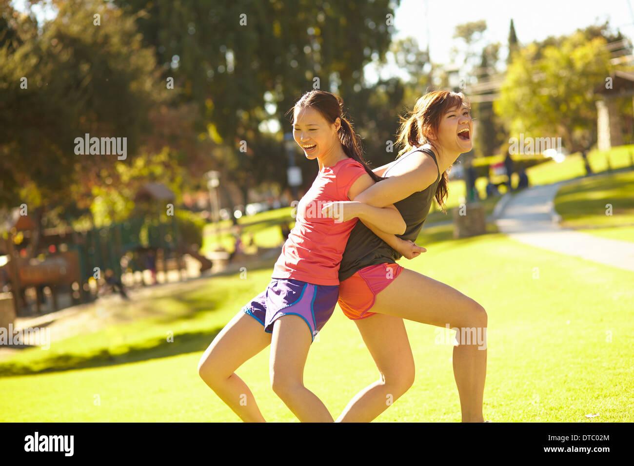 Due giovani donne a braccetto e schiena a schiena in posizione di parcheggio Immagini Stock