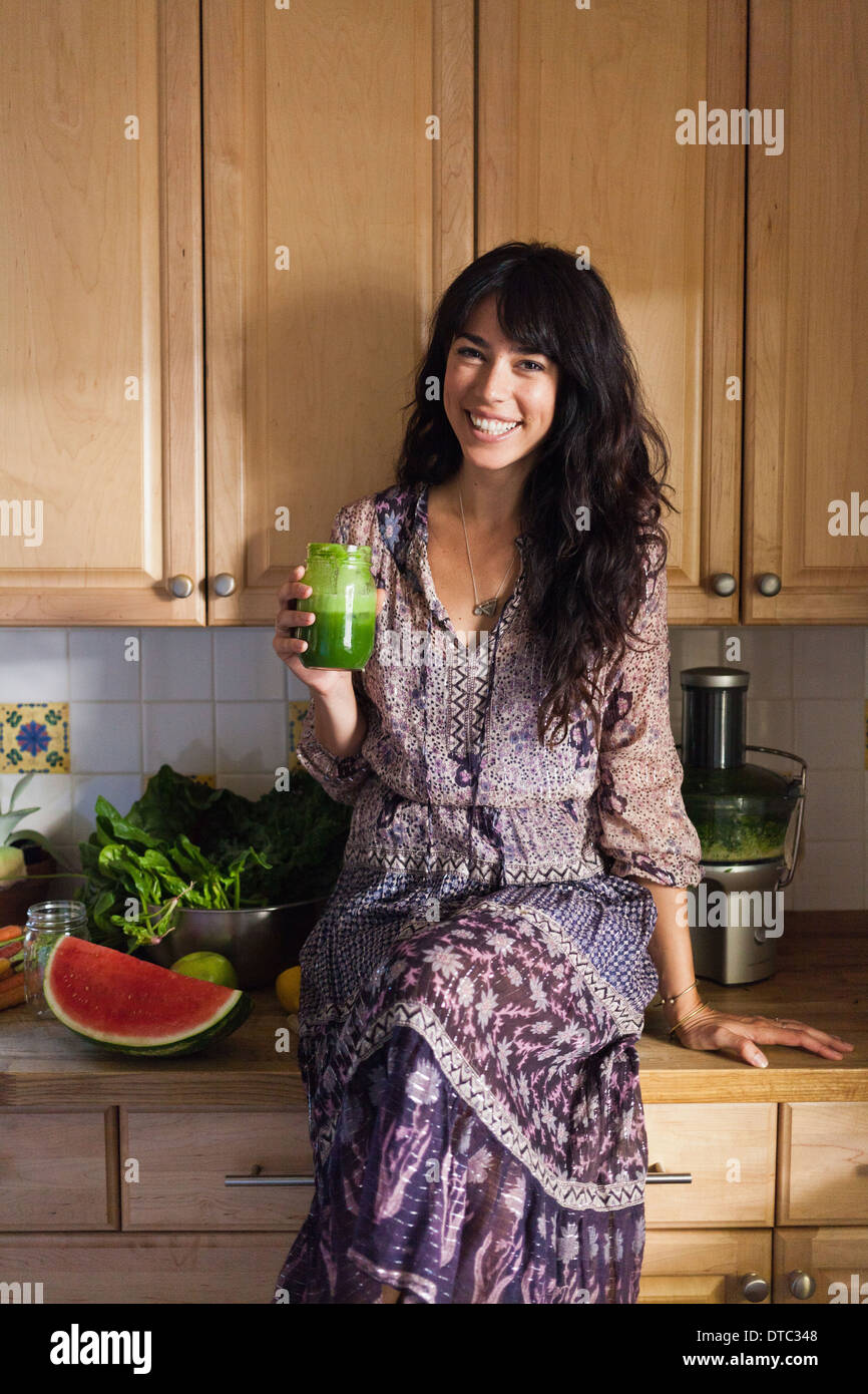 Giovane donna in cucina con succo di verdura Immagini Stock