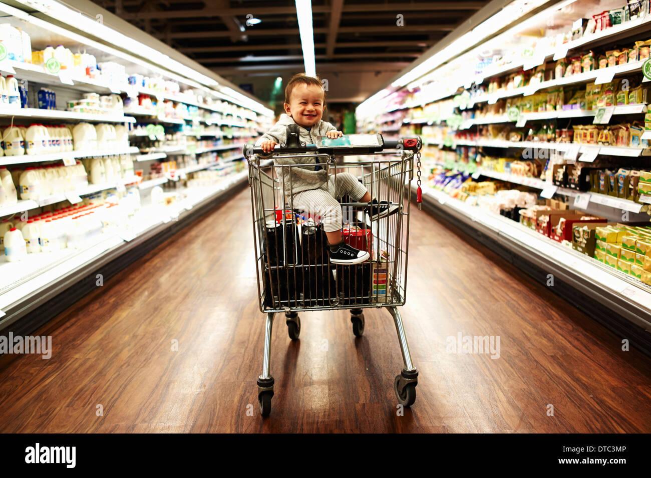 Bambino seduto nel carrello per supermercati Immagini Stock