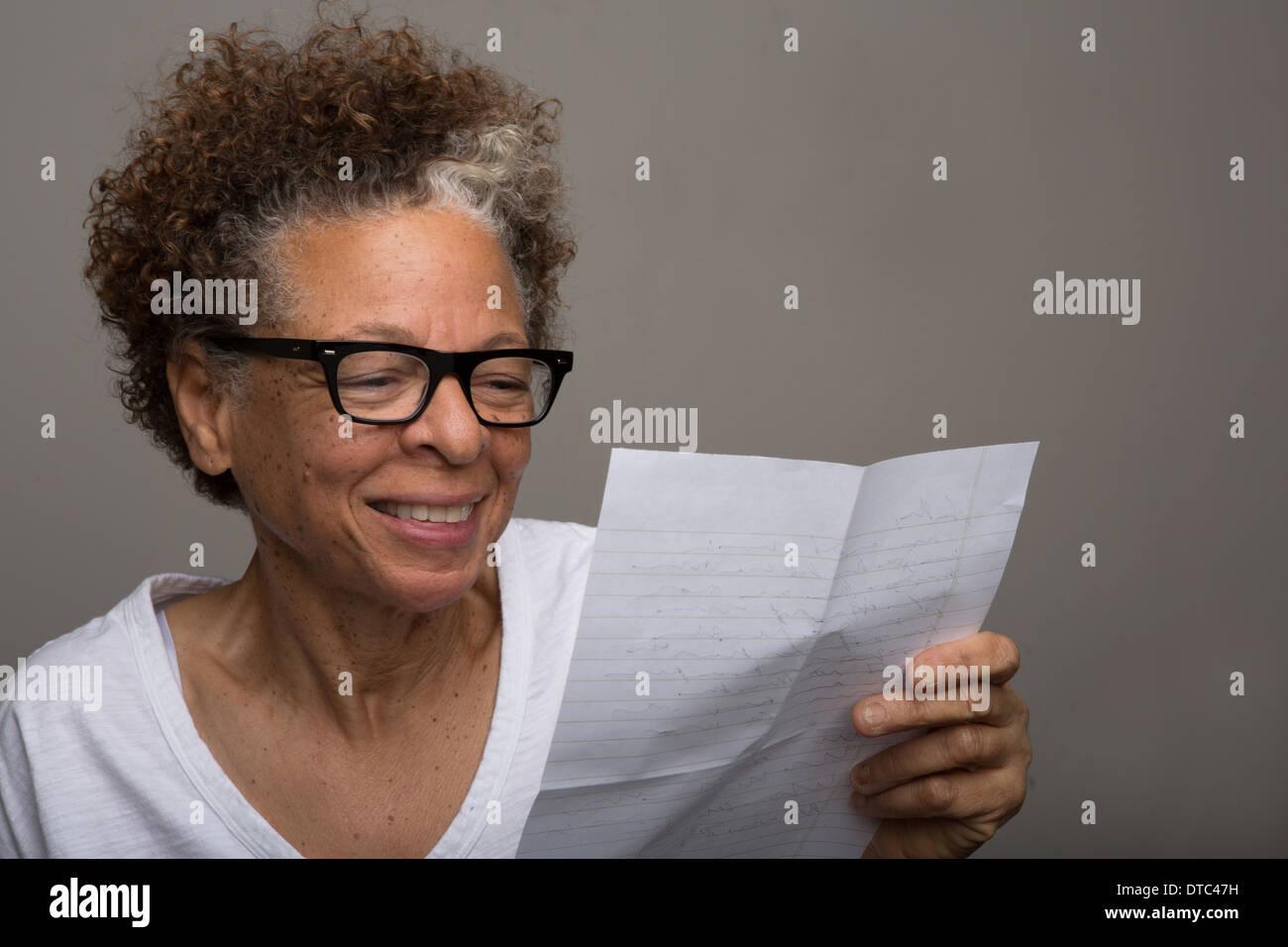Ritratto in studio di Felice senior donna la lettura di una lettera Immagini Stock