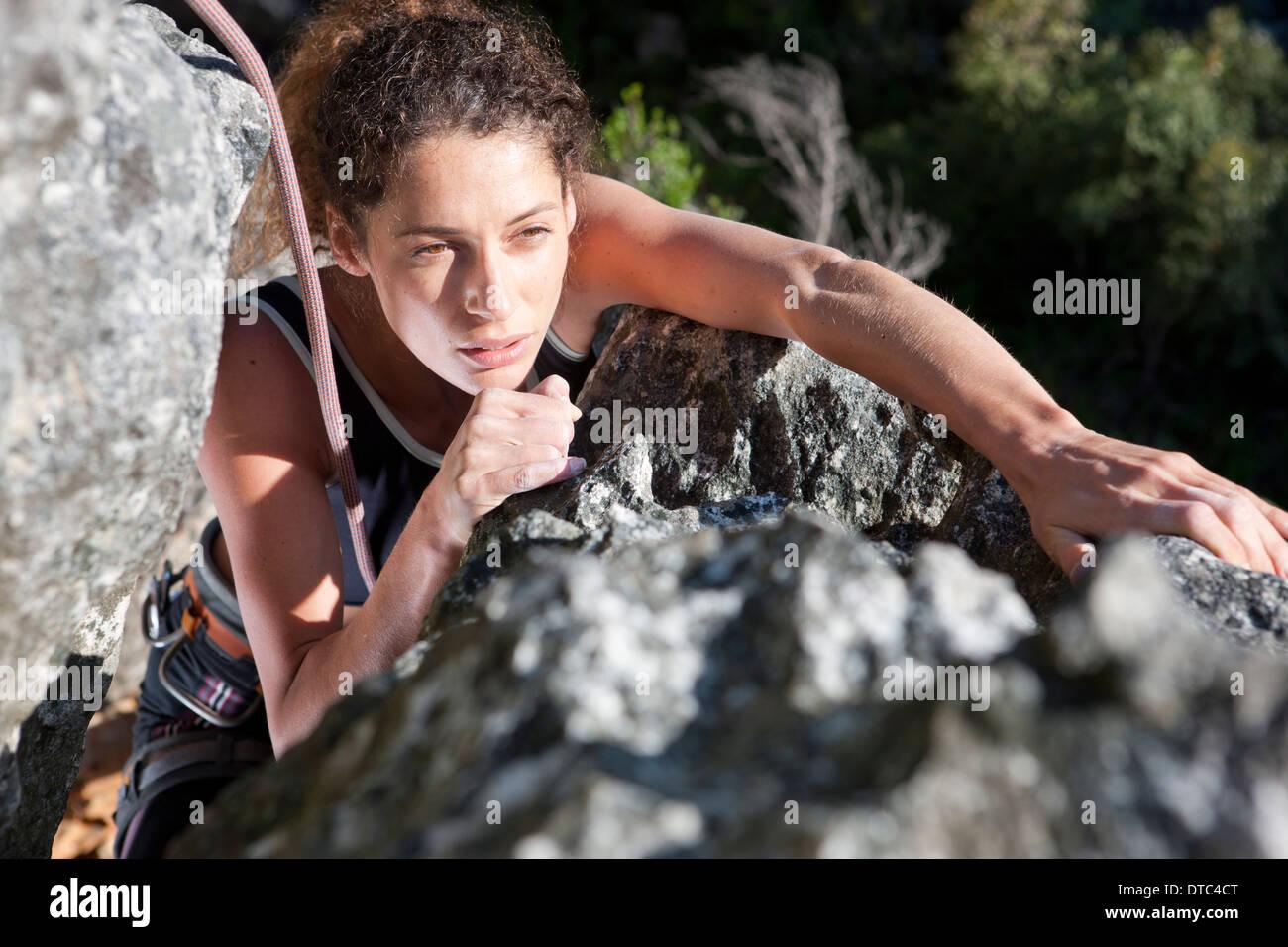 Giovani femmine rocciatore nello spostamento verso l'alto di roccia Immagini Stock