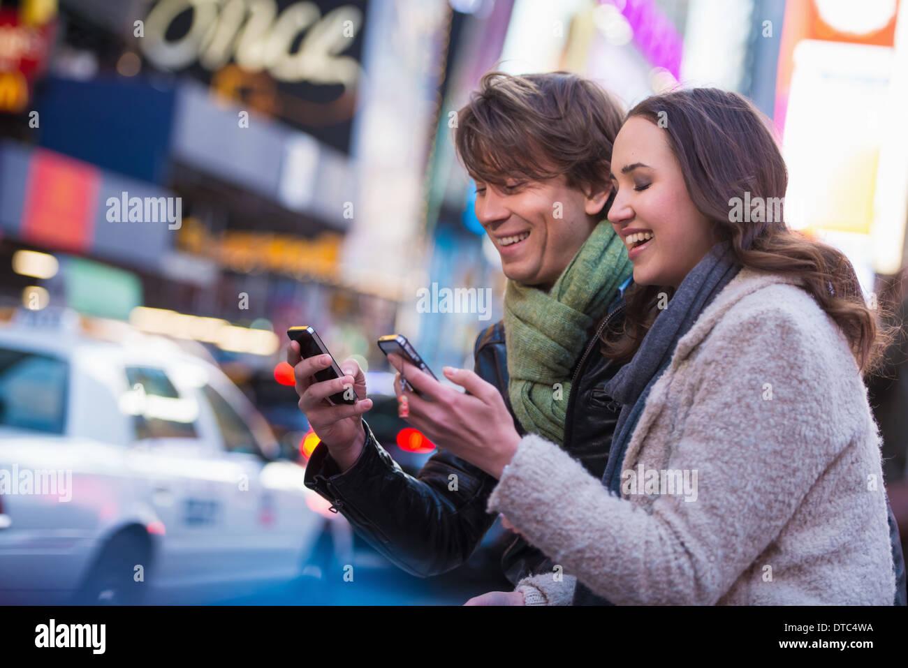 Coppia giovane competere sui telefoni cellulari, New York City, Stati Uniti d'America Immagini Stock
