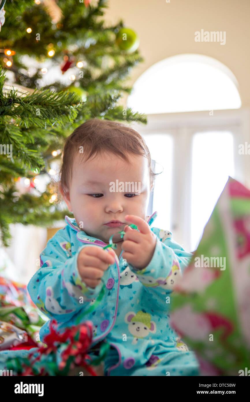 Baby girl aprendo i regali di Natale sul suo primo Natale Foto Stock