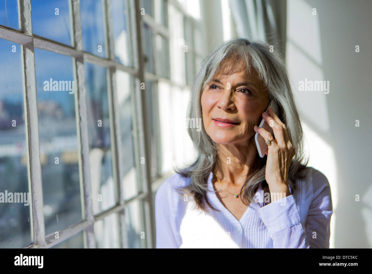 Senior donna guardando fuori della finestra mentre utilizza lo smartphone Immagini Stock