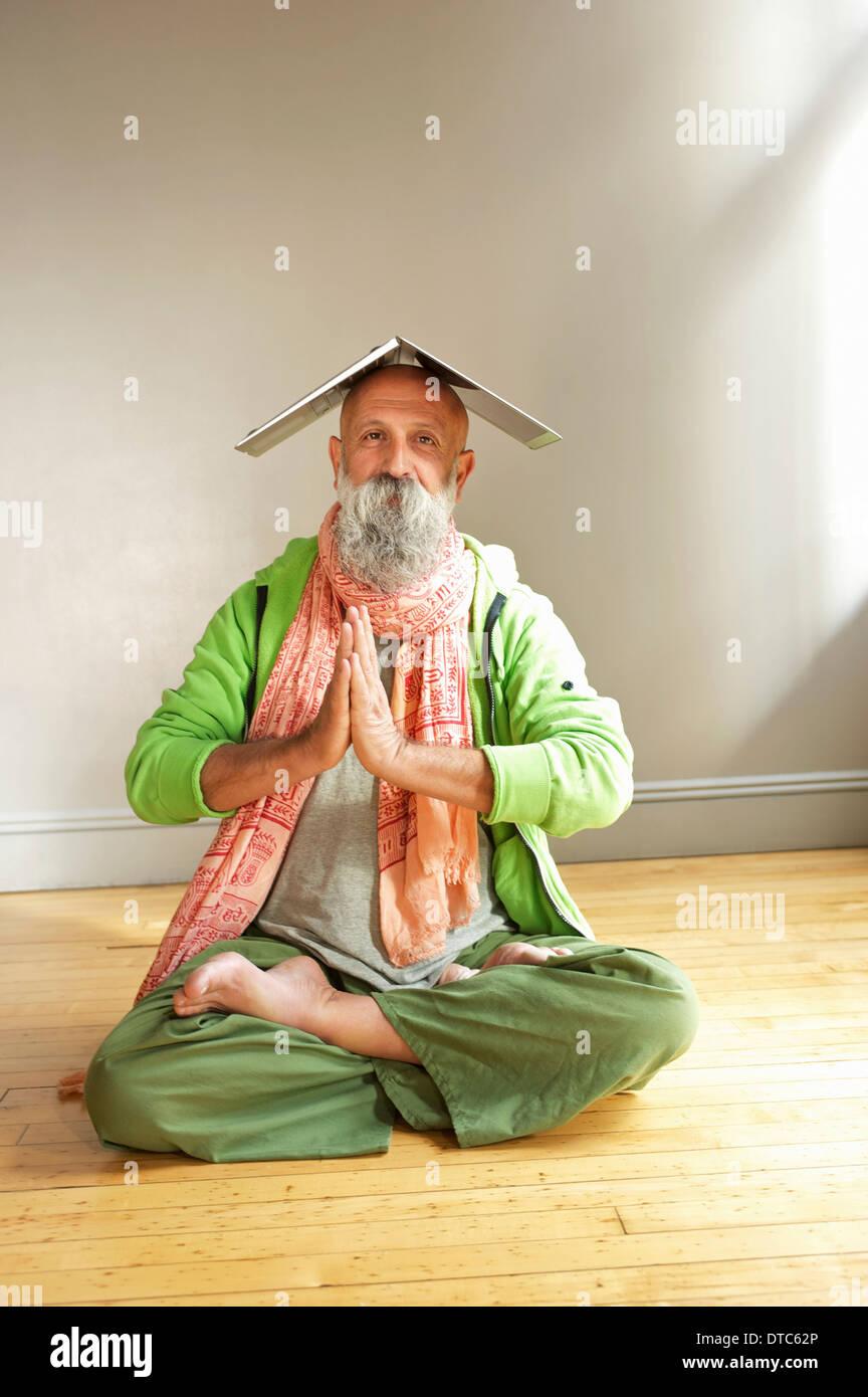 Senior uomo nella posizione del loto con il computer portatile sulla testa Immagini Stock