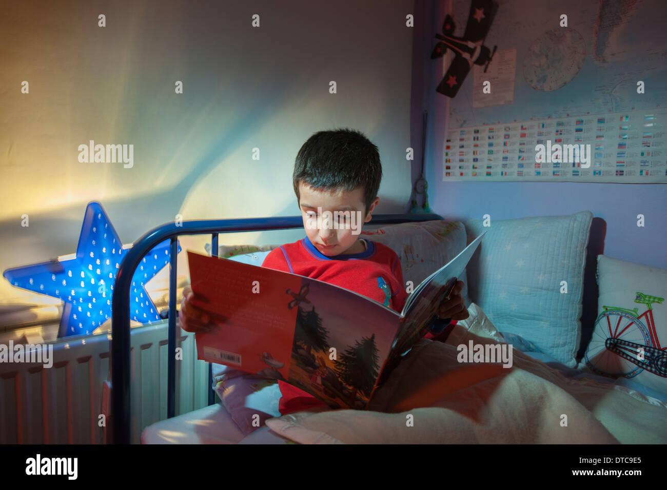 Ragazzo giovane,la lettura di una storia prima di addormentarsi nel suo letto Immagini Stock